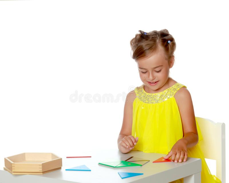 A little girl is studying Montessori stuff. A little girl in Montessori kindergarten sits at a table and studies Montessori stuff. The concept of school and stock photos