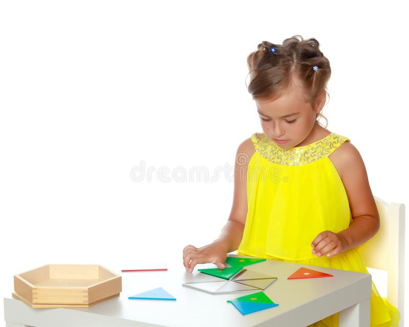 A little girl is studying Montessori stuff. A little girl in Montessori kindergarten sits at a table and studies Montessori stuff. The concept of school and stock image