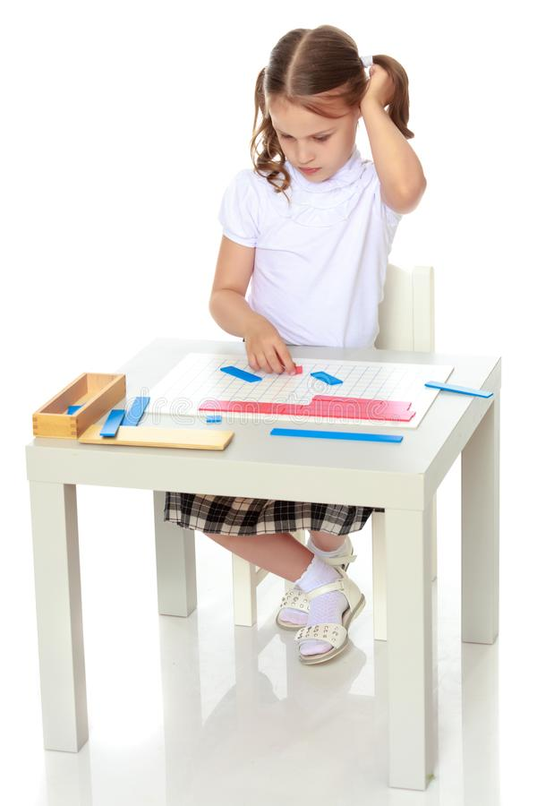 A little girl is studying Montessori stuff. A little girl in Montessori kindergarten sits at a table and studies Montessori stuff. The concept of school and royalty free stock images