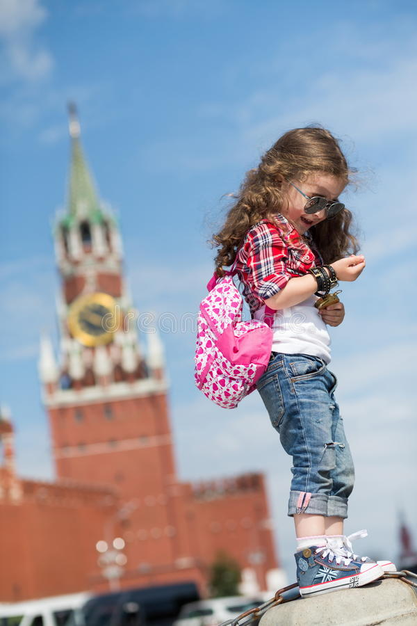 The little girl in stylish dress and sunglasses near the Kremlin stock photo