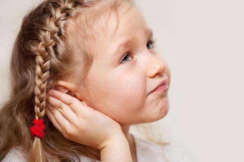 Little girl suffering from otitis. Child has a sore ear. Little girl suffering from otitis stock photos