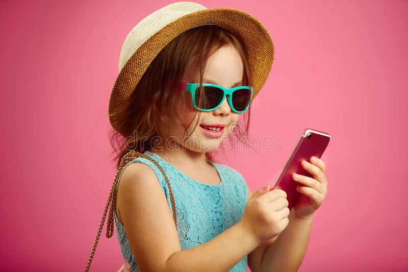Little girl in summer clothes, wearing a beach hat, sunglasses, looking at the phone, stands on pink isolated background stock photography