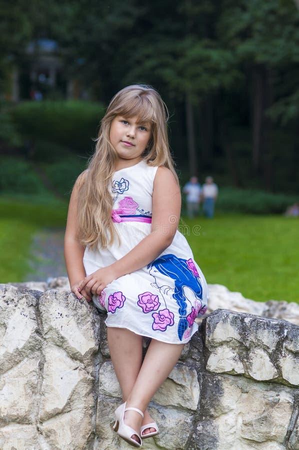 A Little Girl In A Summer Dress Walks In The Park Stock