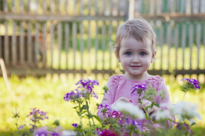 Little girl in the summer garden among the flowers. Smiling royalty free stock image