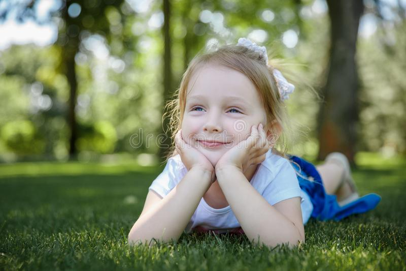 Girl in a summer park lies on the rug on the grass. Little girl in a summer park lies on the rug on the grass stock image