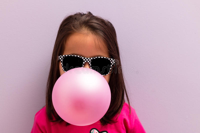 Little girl with sun glasses blowing up pink chewing gum. Against a light purple background royalty free stock image