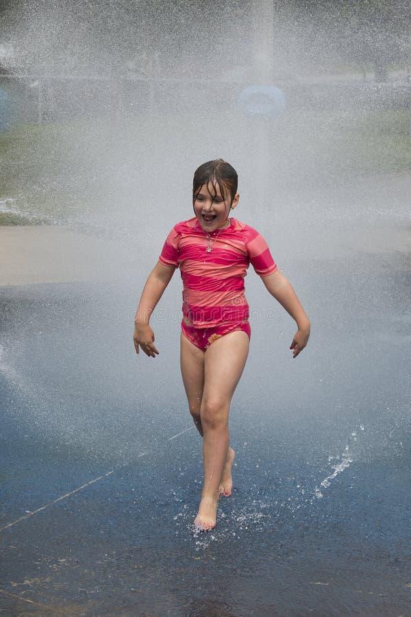 Little girl in sun suit running in children's park water games stock images
