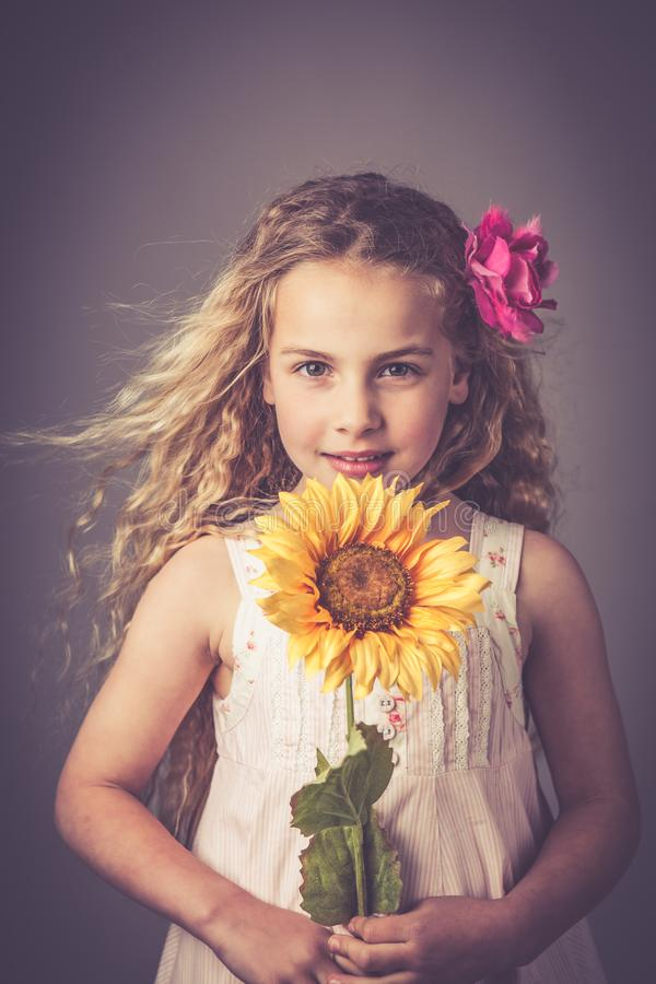 Little girl with a sunflower royalty free stock image