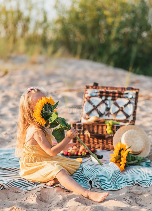 Little Girl with Sunflower, Summer picnic in the beach. Wooden basket with food royalty free stock images