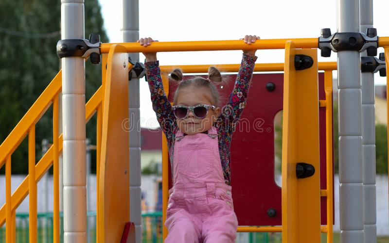 Little girl in sunglasses on playground royalty free stock photography