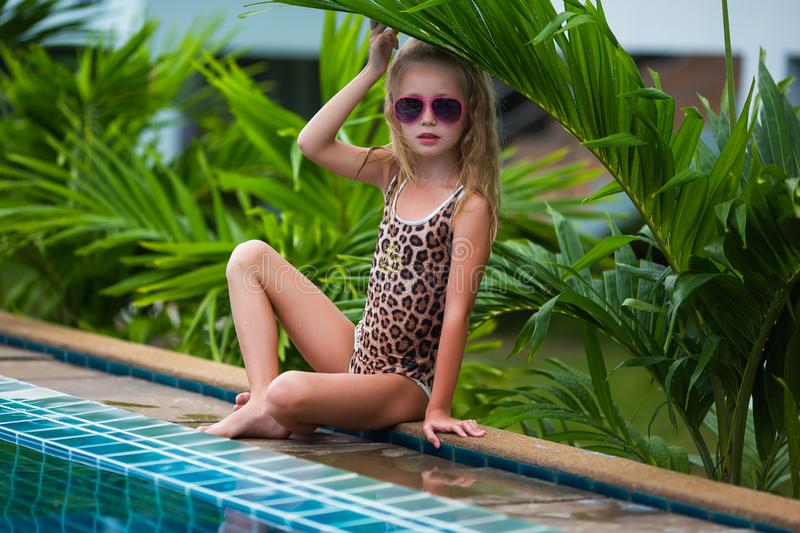 Cute little girl in sunglasses in pool in sunny day stock photo