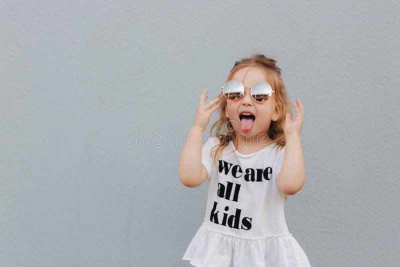 Little girl in sunglasses posing to photographer. Blond hair female child ountside stock photos