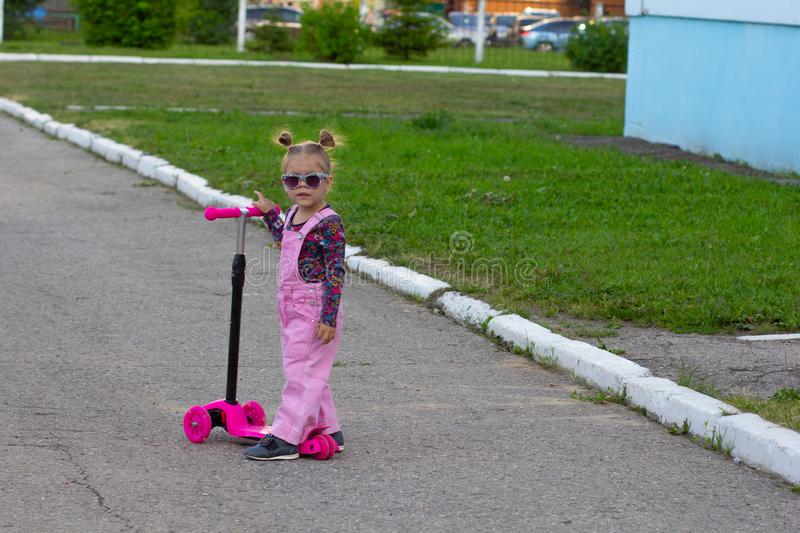 Little girl in sunglasses on scooter on playground stock photo