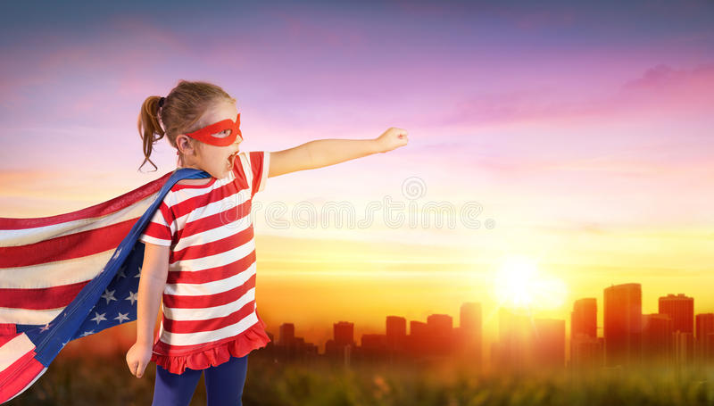 Little Girl Superhero Of Usa With Cityscape royalty free stock photos