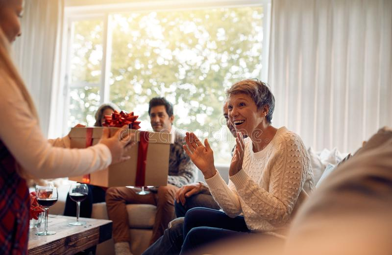 Little girl surprising her grandmother with a christmas present stock image