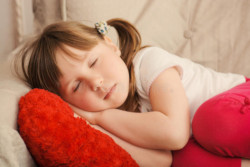 Little girl with sweet dreams sleeping in the chair. Little girl with sweet dreams sleeping holding hands together on the red pillow in chair stock images