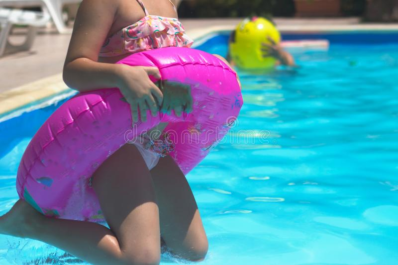 Little girl with swim ring jumps in the pool. Summertime background with copy space royalty free stock images