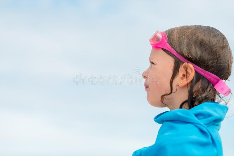 Little girl in swimming glasses wrapped in a towel - after swimming in the sea royalty free stock photos