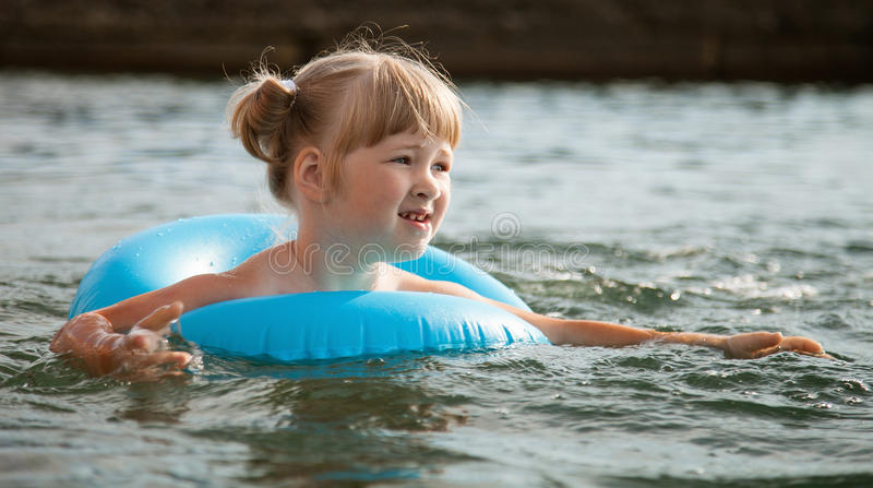 Little girl swimming with inflatable circle. Smiling little girl swimming with inflatable circle stock photo