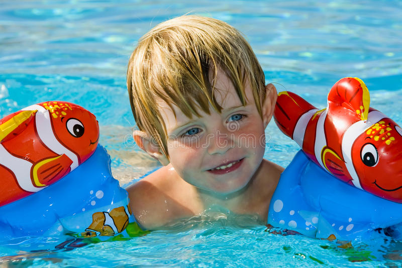 Little girl in the swimming pool. Pretty little girl swimming in outdoor pool stock photo
