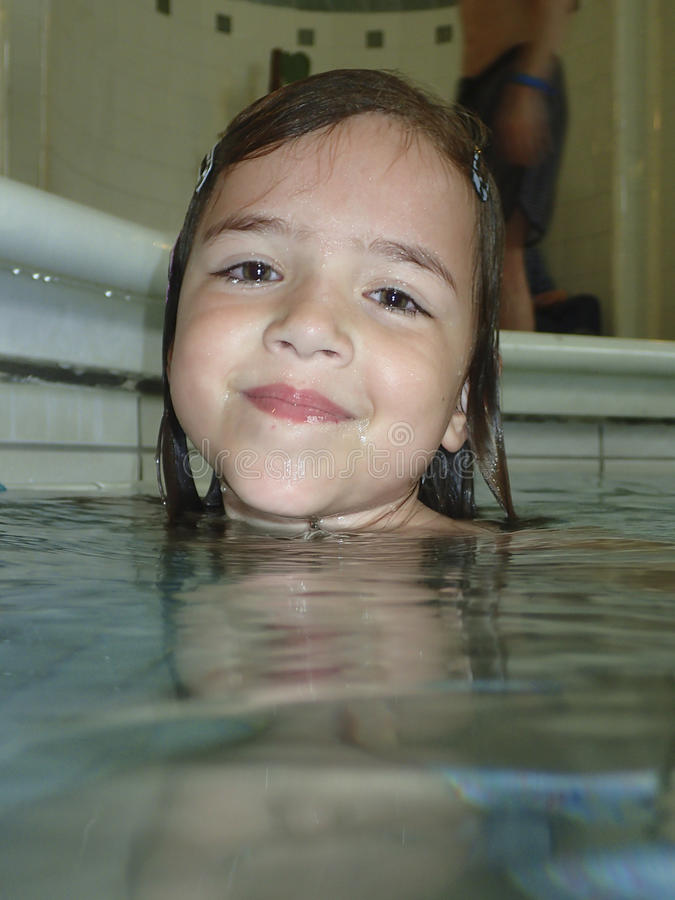 Little girl at the swimming pool stock photo