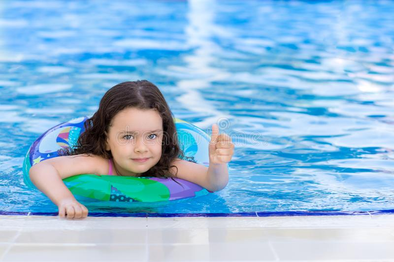 A little girl is swimming in the pool with inflatable ring and showing thumb`s up gesture. Kids learn to swim stock photos