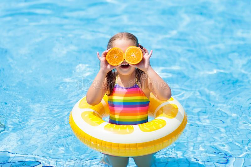 Child in swimming pool. Kid eating orange. stock images
