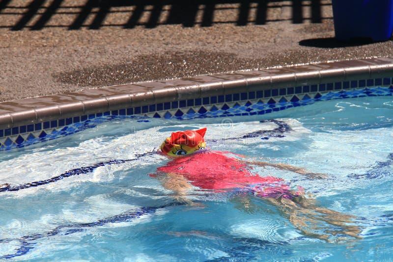 Little girl swimming in pool stock photo