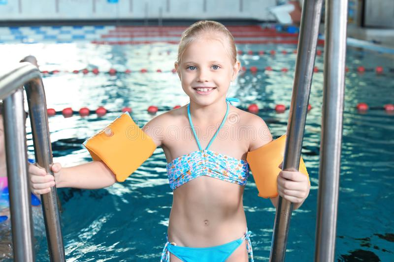Little girl with swimming sleeves. In indoor pool stock photos