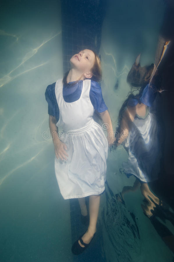Little girl swimming underwater in dress stock photography