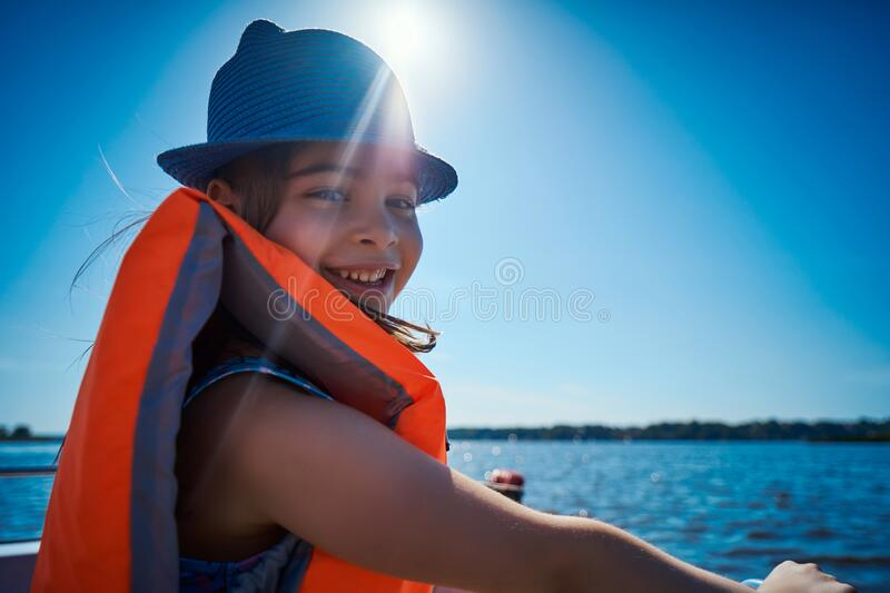 Little girl in a swimming vest sits in a motorboat royalty free stock images