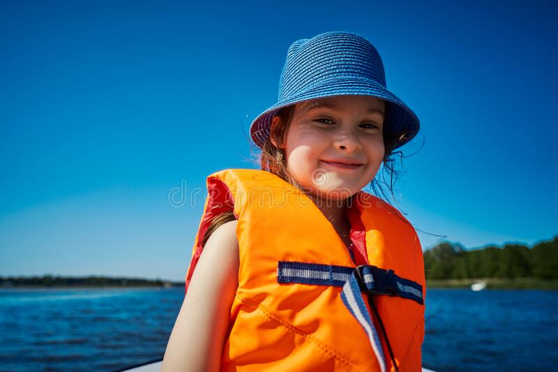 Little girl in a swimming vest sits in a motorboat royalty free stock photography