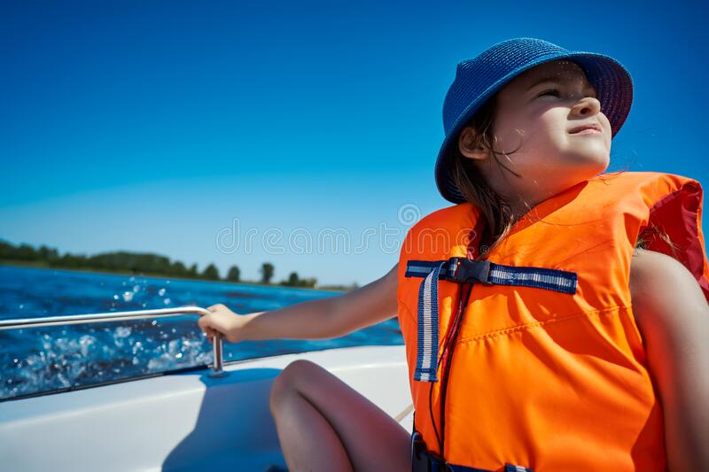 Little girl in a swimming vest sits in a motorboat stock image