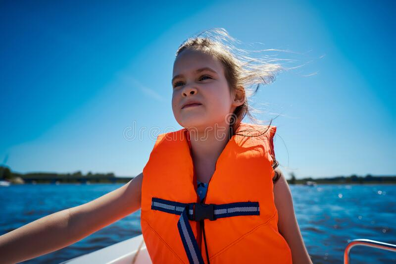Little girl in a swimming vest sits in a motorboat stock photo