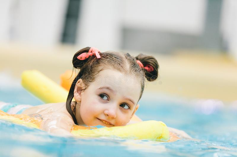 Little girl swimming with a yellow noodle in a pool. stock photography