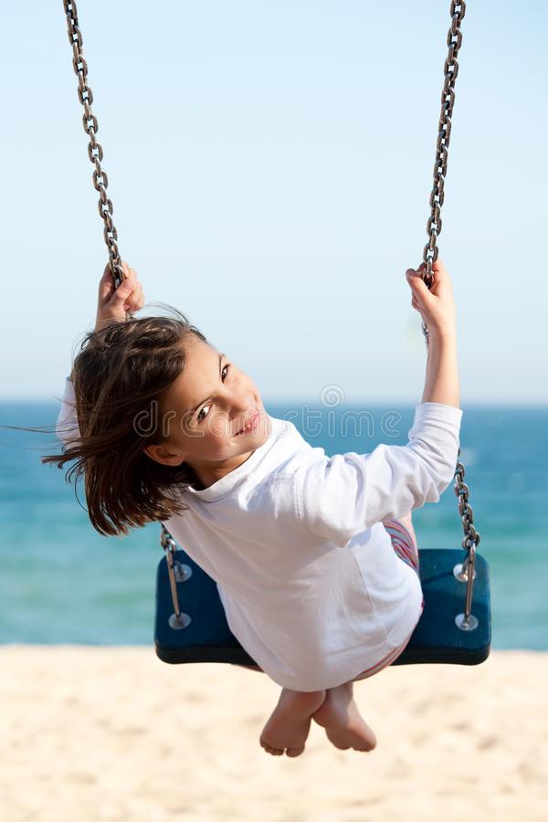 Little girl swinging. With the sea in the backgroun stock photo
