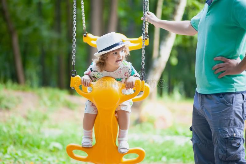 Little girl is swinging at play ground outdoors, sunny day. Little girl is swinging at play ground with her father, sunny day royalty free stock photos