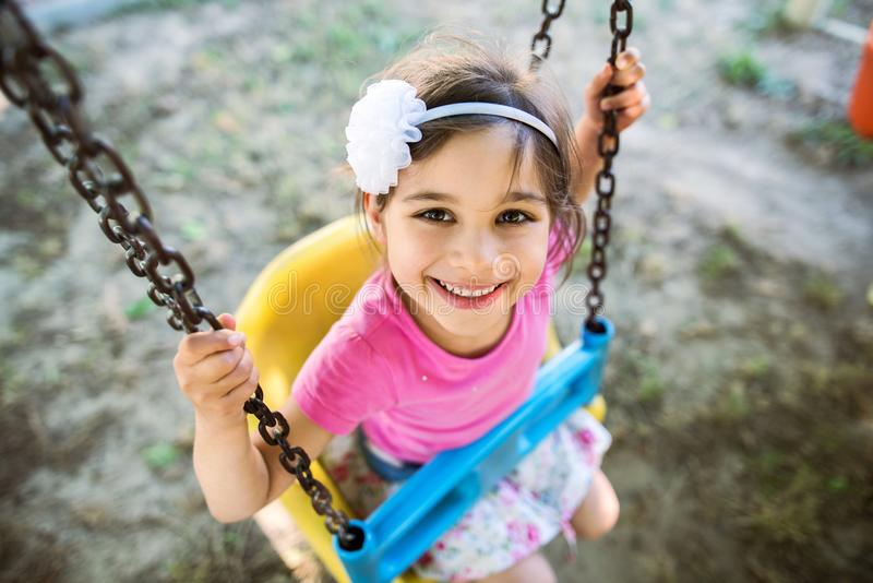 Little Girl Swinging At Playground Outdoors royalty free stock images