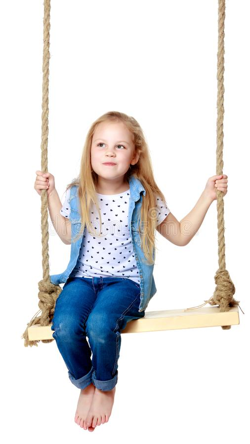 Little girl swinging on a swing royalty free stock photos