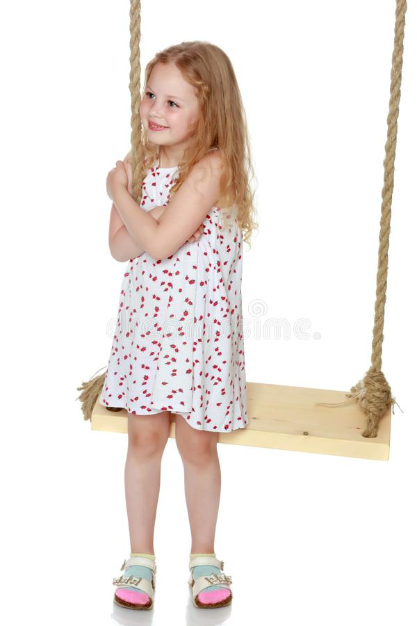 Little girl swinging on a swing stock images