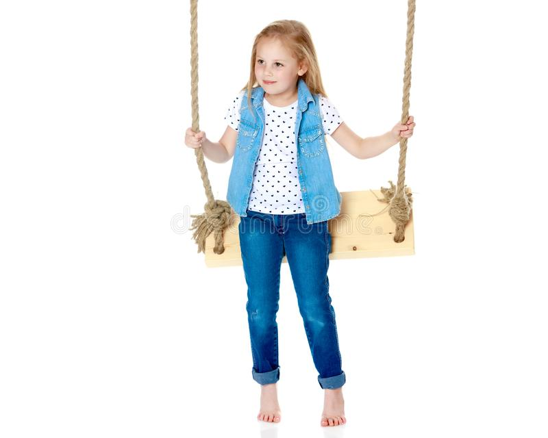 Little girl swinging on a swing stock photos