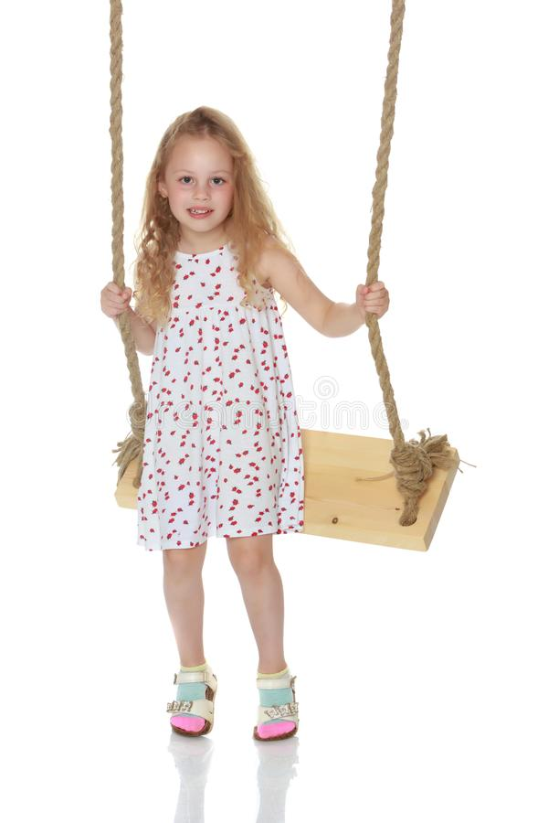 Little girl swinging on a swing. Isolated on white background royalty free stock image