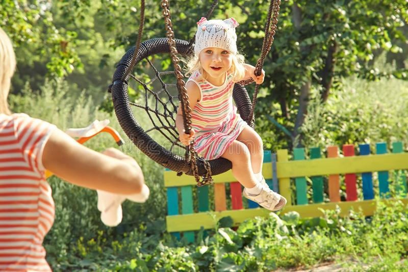 Little girl swinging on a swing royalty free stock photo
