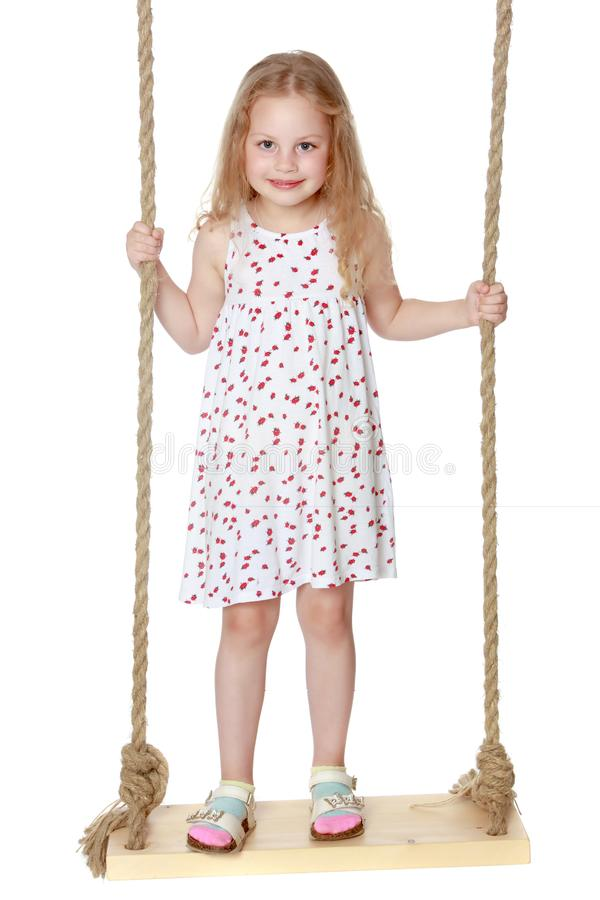 Little girl swinging on a swing royalty free stock images