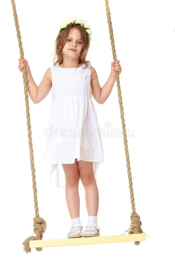 Little girl swinging on a swing stock image