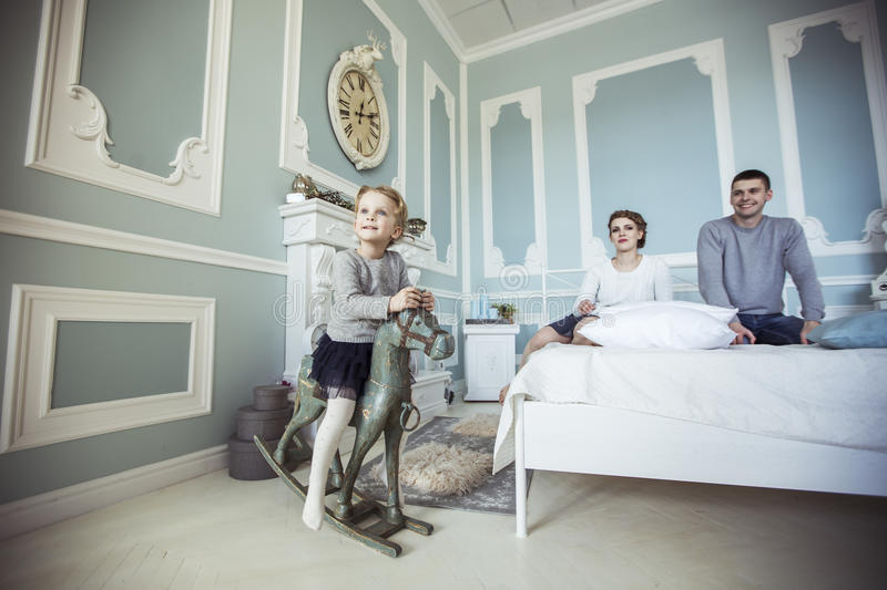 Little girl swinging on a wooden horse in the bedroom of their parents stock photo