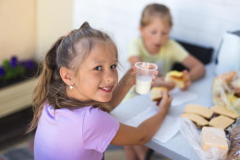 Little girl at the table eats a pie with milk stock photo