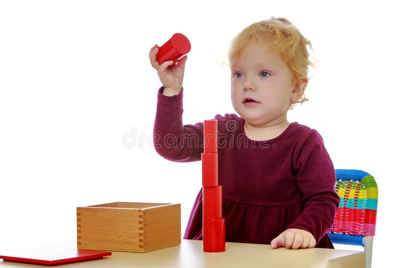 The little girl at the table works with the Montessori material. stock image