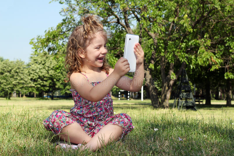 Download Little Girl With Tablet In Park Stock Images - Image: 25870904