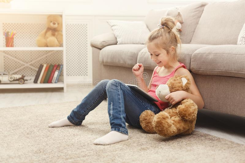 Little girl with tablet sitting on the floor at home stock photos